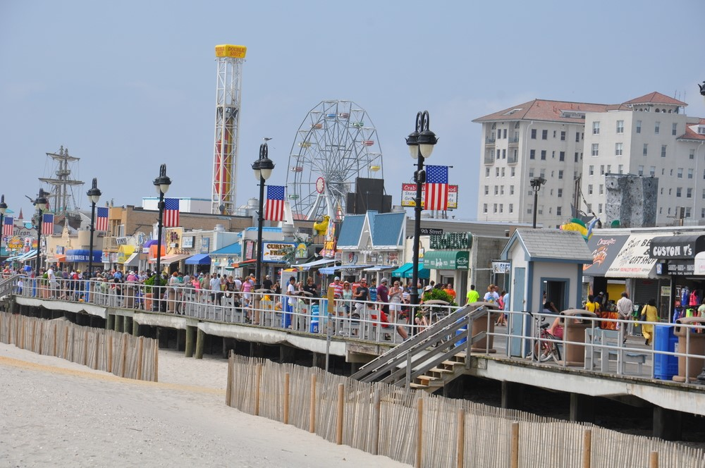 Stores and a fair along the boardwalk in Ocean City where you can see the sky and the sand