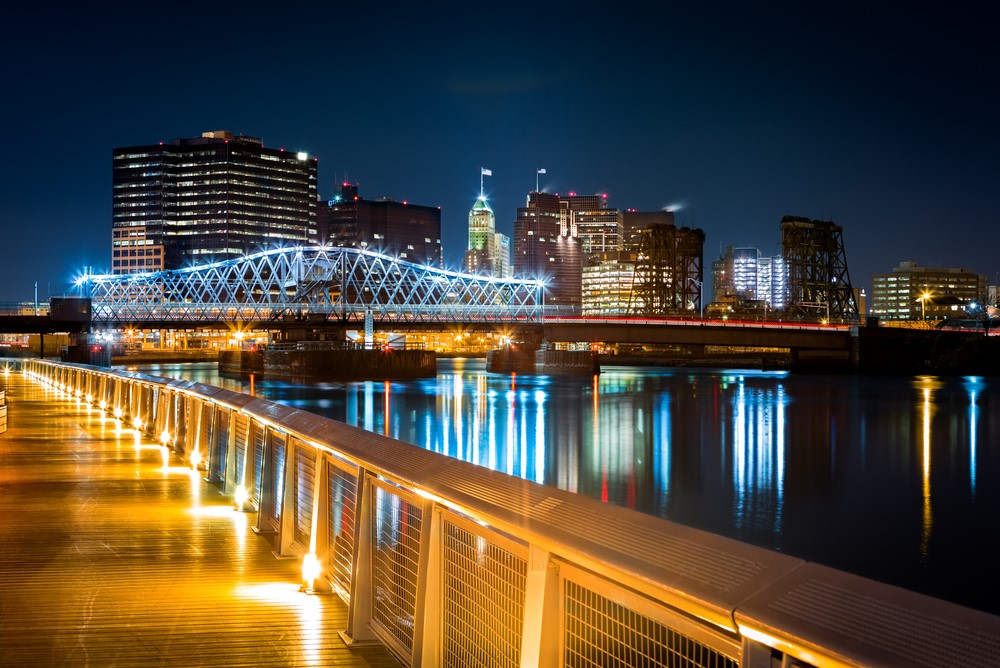 The cityscape of Newark New Jersey at night where the lights of the city are reflecting in the water
