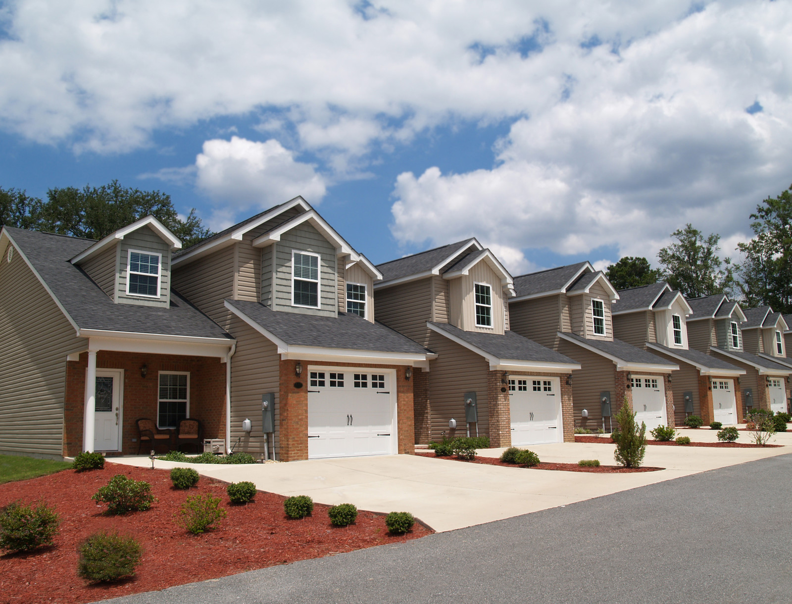 Two story townhomes in a retirement community with mulch in the front yard dotted with immature shrubs