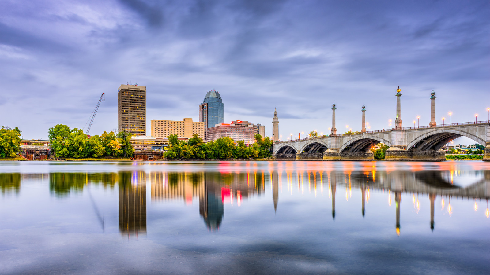 downtown skyline of Springfield, Massachusetts, photo take from across the Connecticut River in the evening with the lights and skyline reflecting off the water