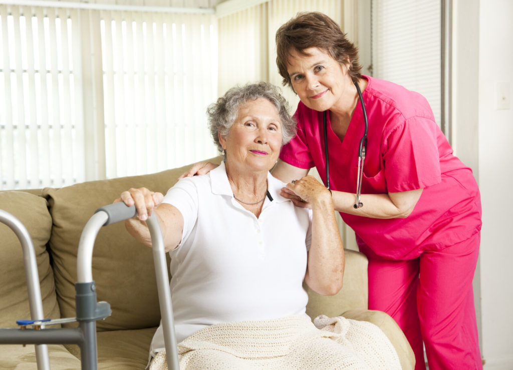 Assisted Living Scams - senior woman sitting on the couch at an assisted living facility with a care giver posing in the photo with hands on her shoulder