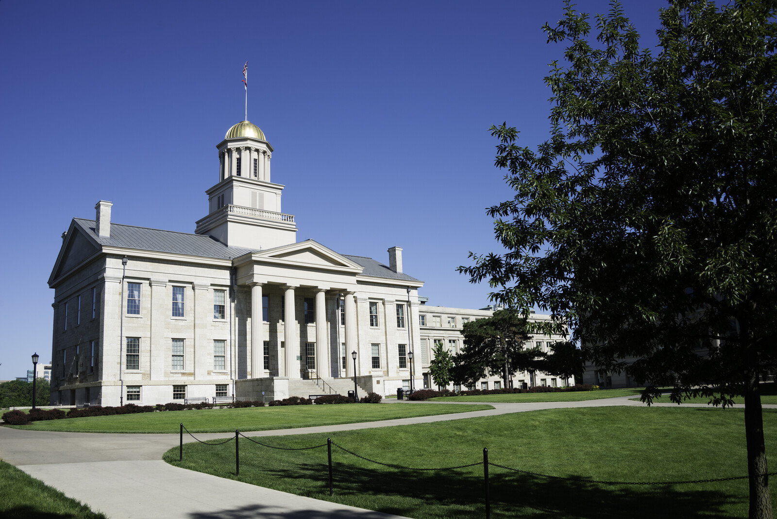 Historic state house with green grass and trees surrounding the building and blue skies on the university of Iowa campus in Iowa city