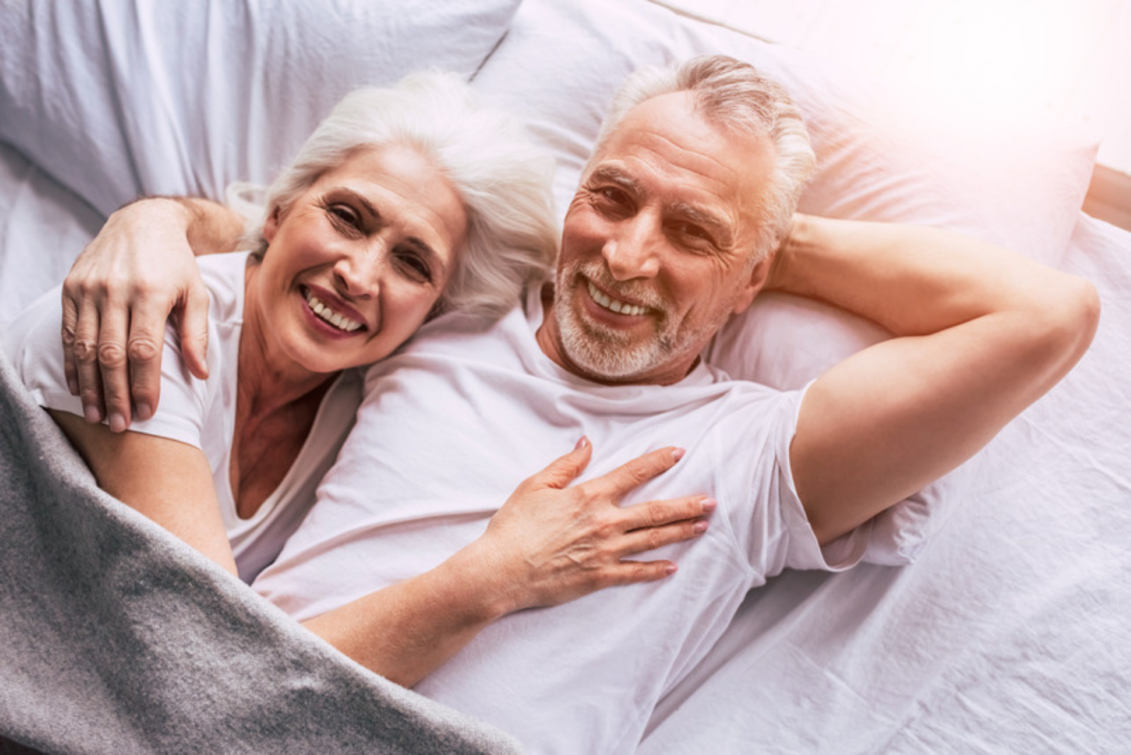 Top Mattresses  for Seniors- smiling senior couple looking into the camer lying in bed on white sheets with a a light gray blanket