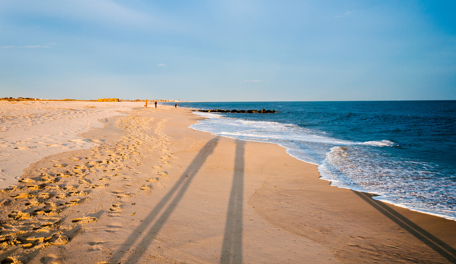 three people walking along the Beach on a sunny day with soft waves rolling onto the sand