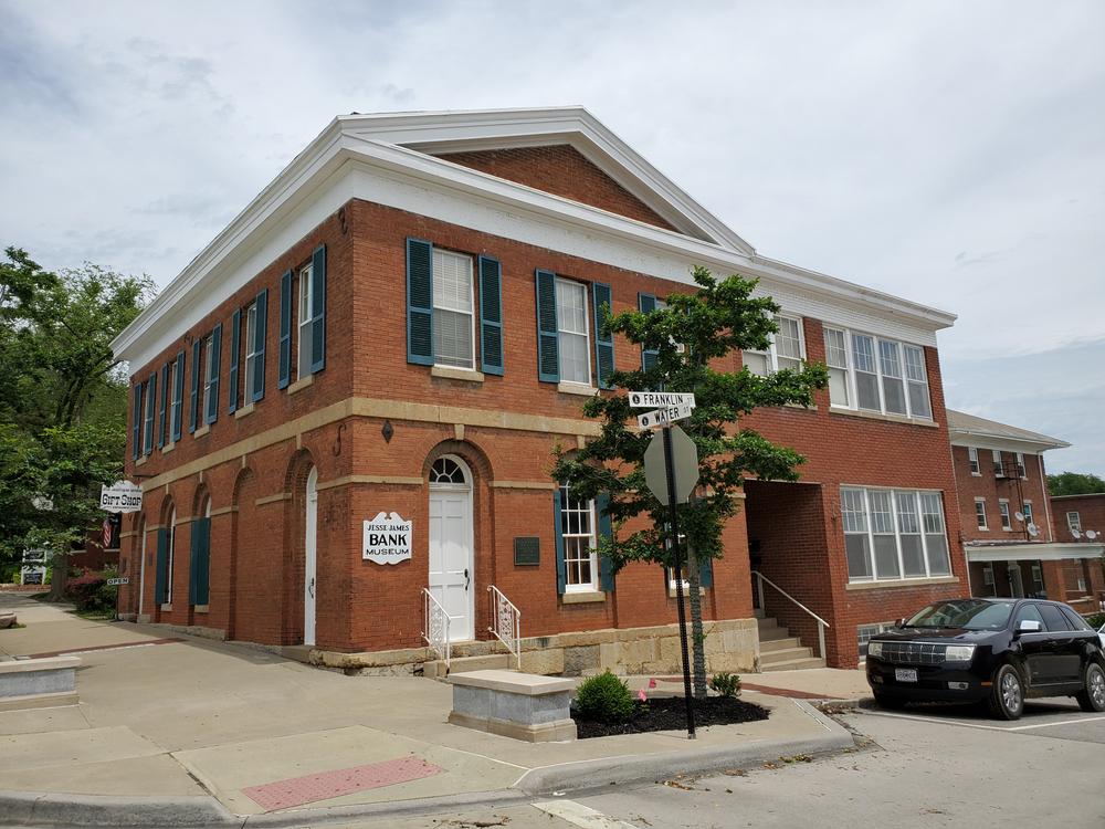 A historic red brick bank in Liberty Missouri against a cloudy sky