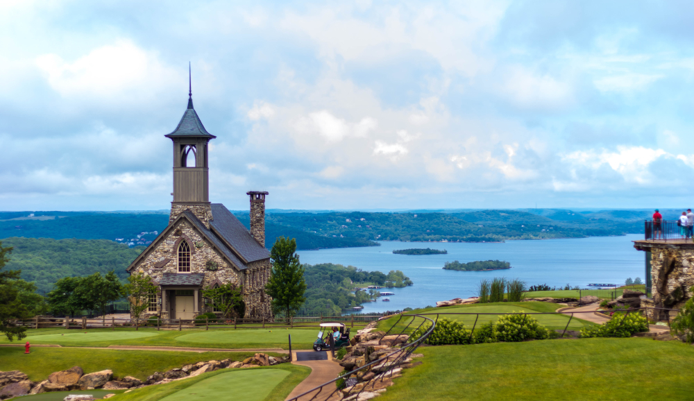 A stone church in Branson Missouri that's on top of a hill, overlooking the water against a cloudy blue sky