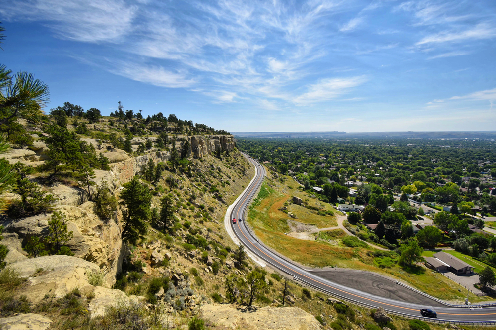 A winding road on a hill in Billings Montana where you can see the blue sky with clouds and plenty of trees on the landscape