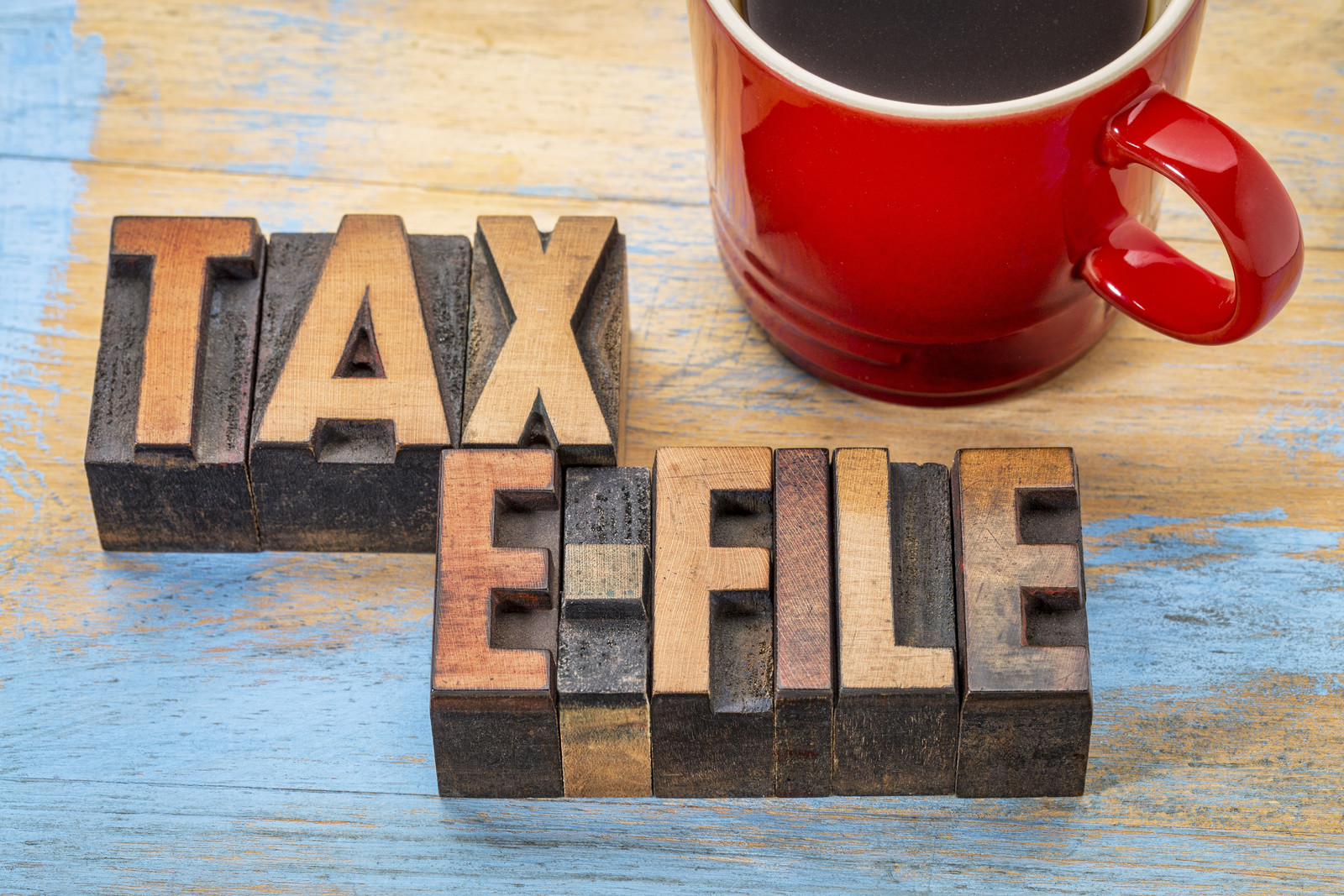 Distressed table with wood block letters that spell out Tax E-File and a red coffee cup in the upper right corner