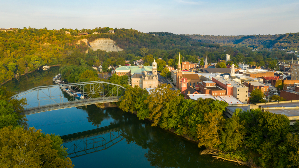 The left side of the image shows a river and a forest, while the right shows downtown Frankfort