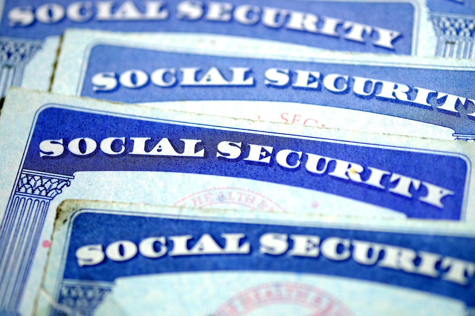 Close up of Four social security cards overlapping one another