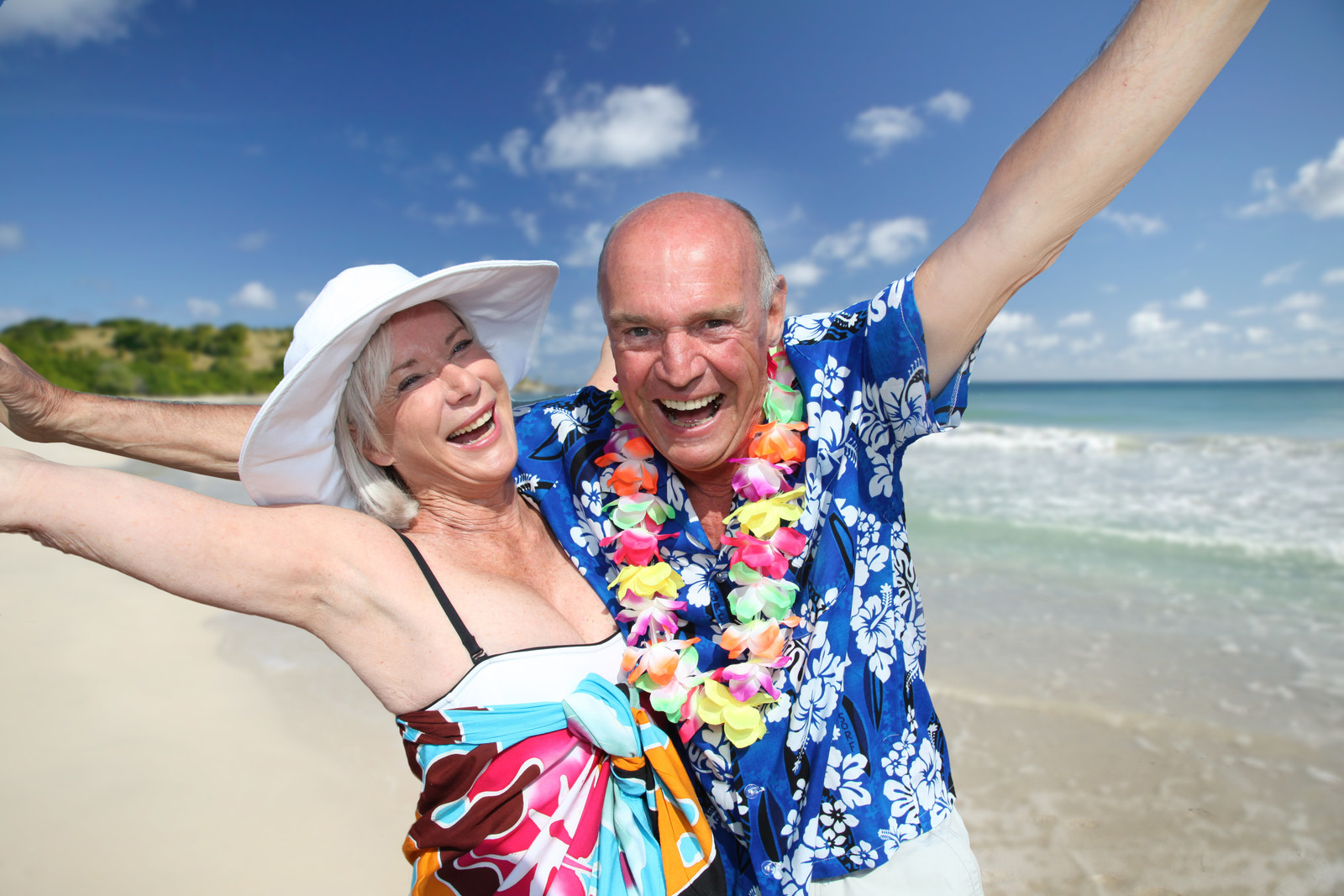 Happy Senior couple on the beach under a blue sky with the ocean in the background
