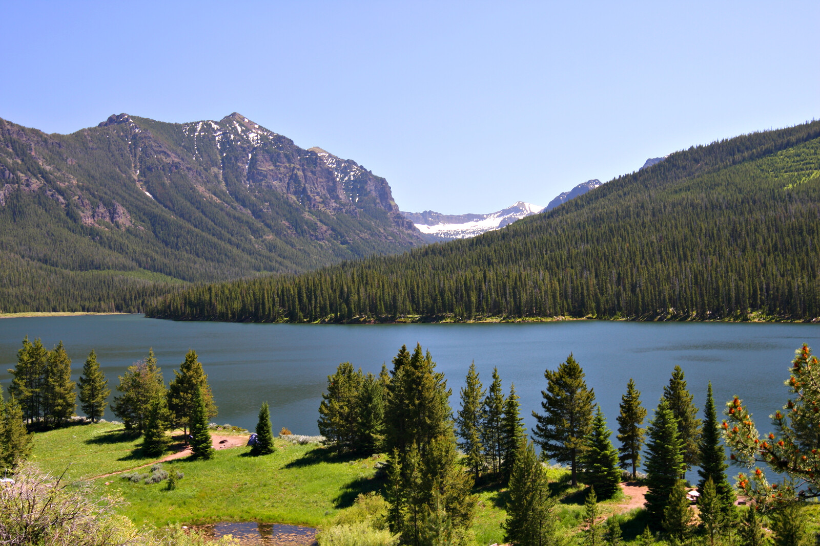 Highlite lake in gallatin national forest, blue skies, mountains in the background, and pines lining the lake in Bozeman, Montana