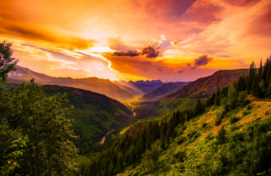 Top 5 Places to Retire in Montana- Montana mountain range at sunrise with orange skies purple mountains, green hills, and a valley with a river running through it.