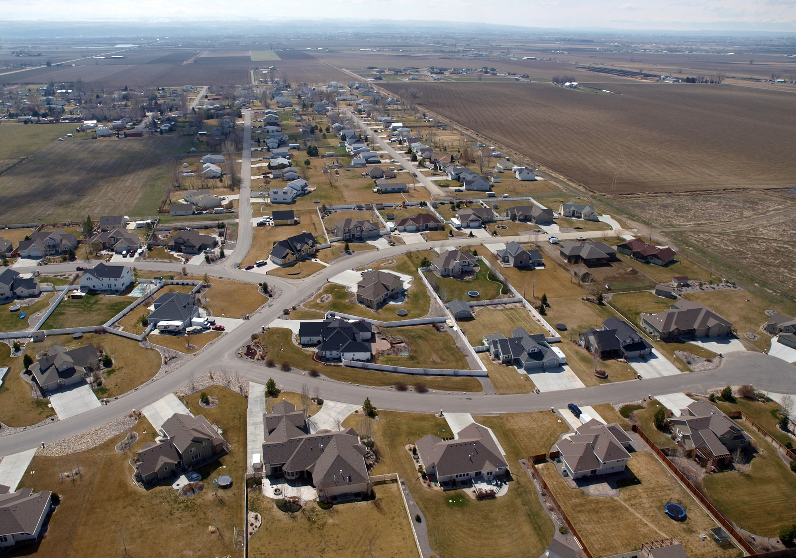 Suburbs in the farmland with new construction houses and farms framing the streets