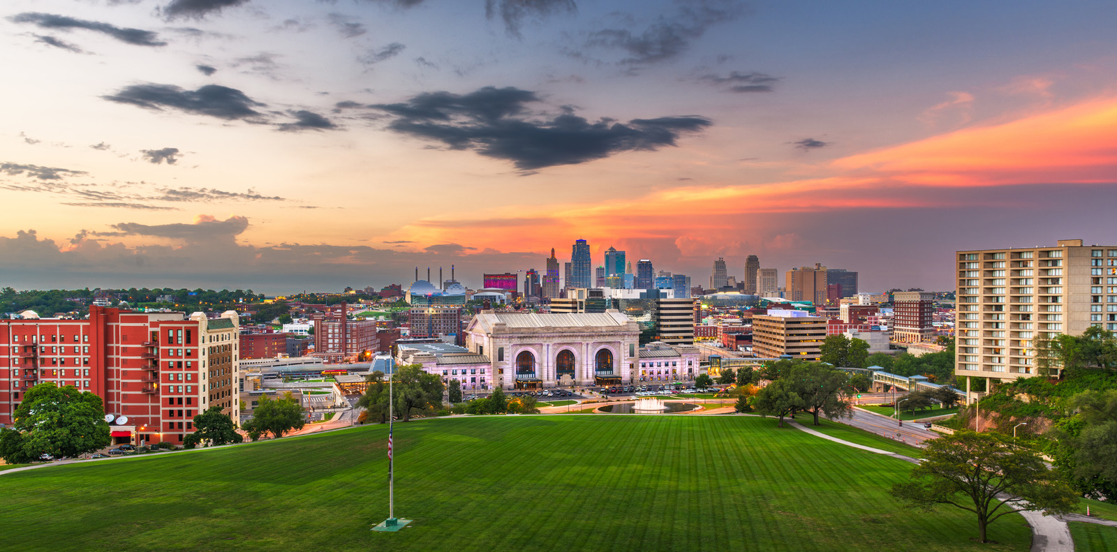 Photo from National Memorial WWI Park with lush green grass and beautiful trees lining the green  of Kansas City Missouri skyline with union station at the center