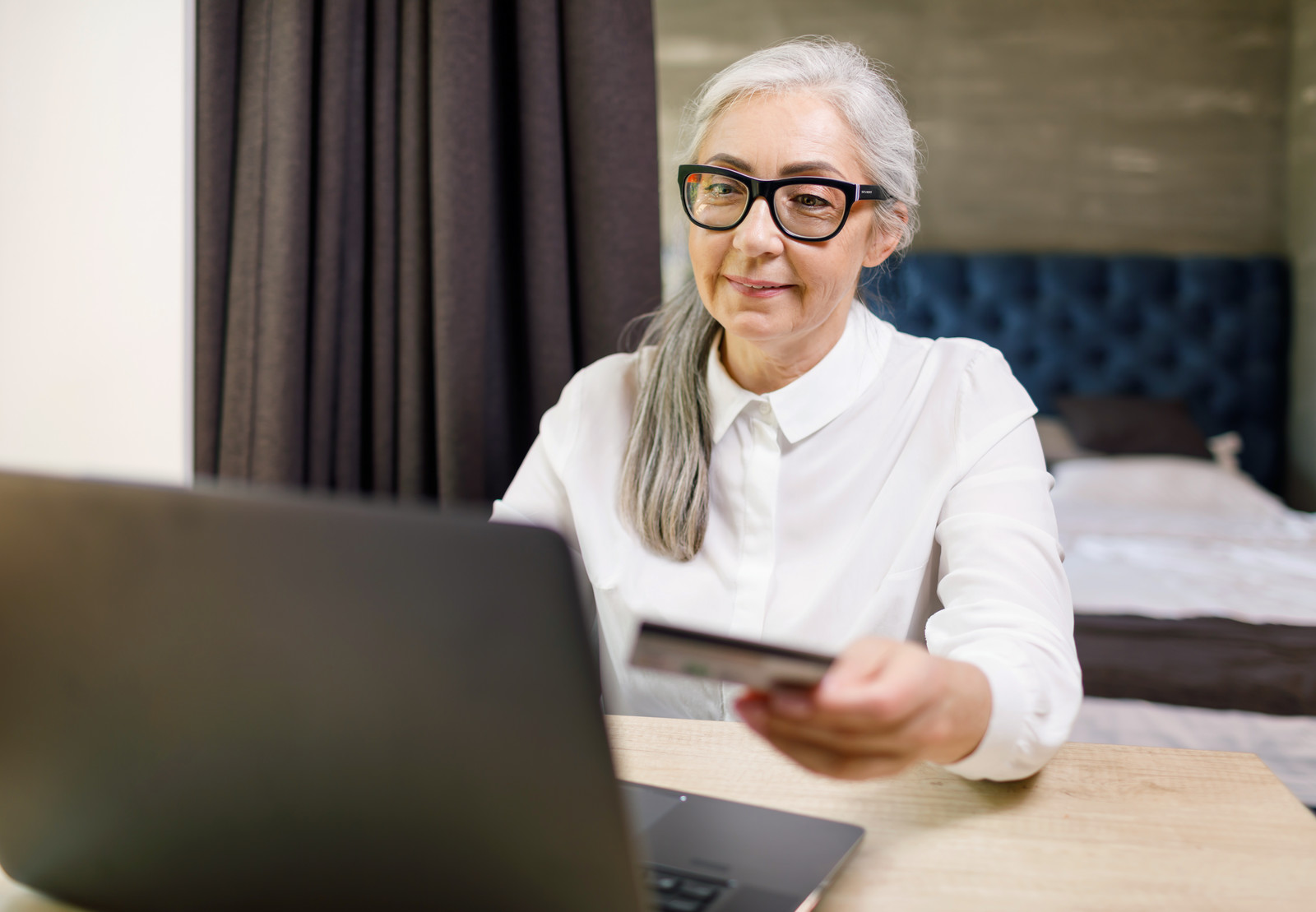 Smiling Senior woman with a credit card in her hand purchasing something on her computer