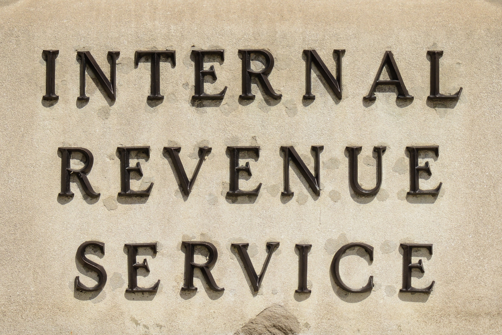 Stone wall of the the IRS building displaying dark letters that state Internal Revenue Service