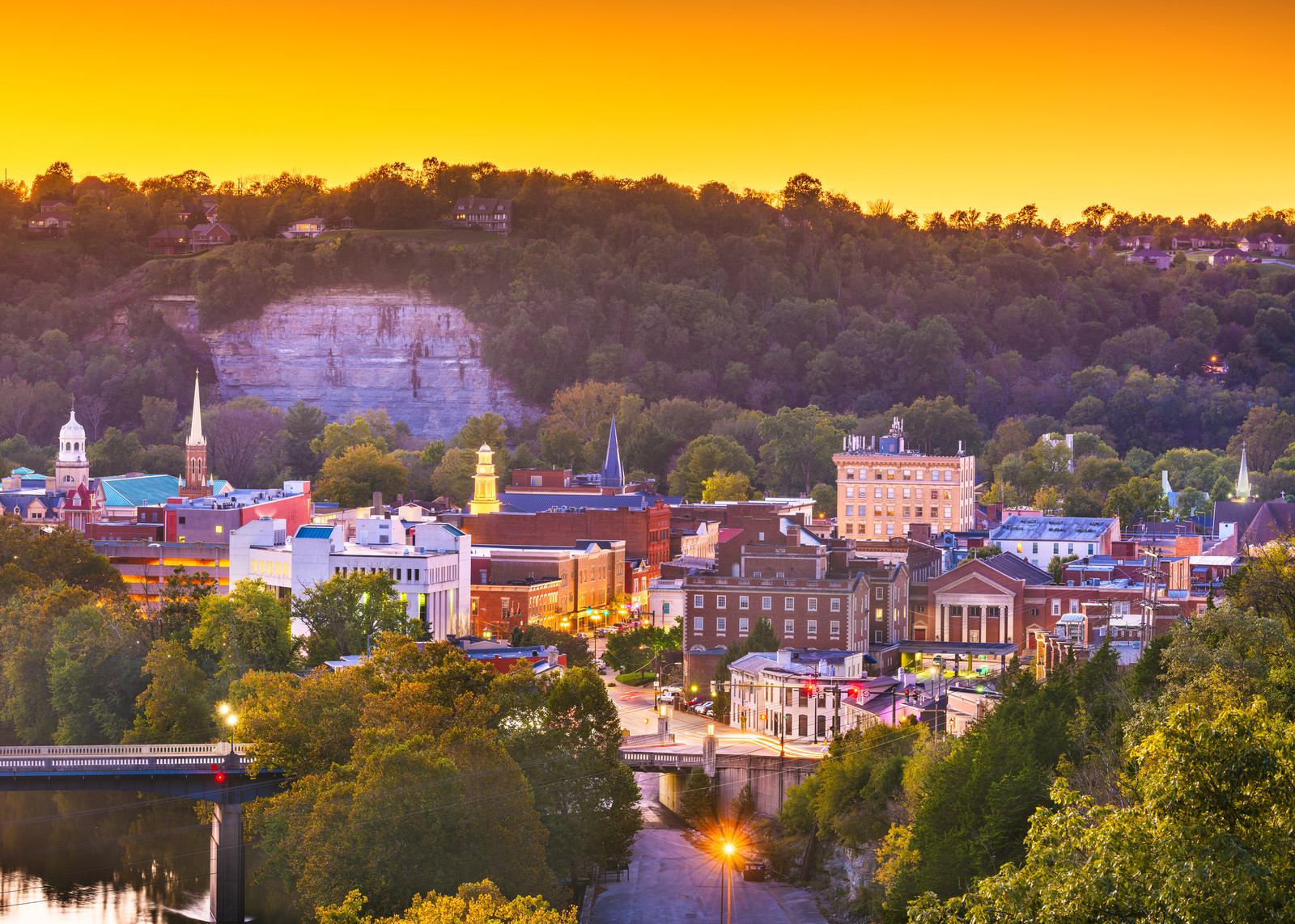 View of Frankfort Kentucky along the Kentucky river from above at sunset, with the sky shades of yellow