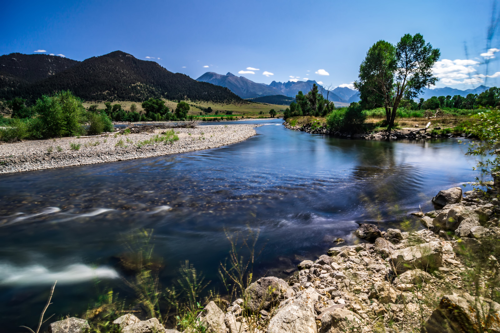 Yellowstone river on a bright day with blue skies and mountains in the background with rocky shores