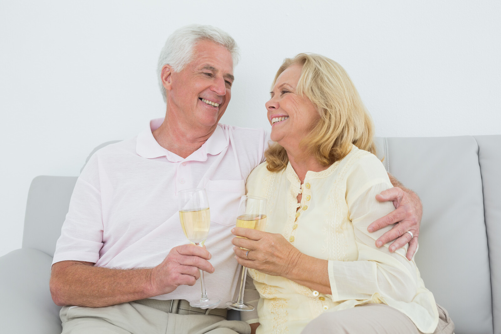 happy senior couple on a couch drinking champagne as if celebrating