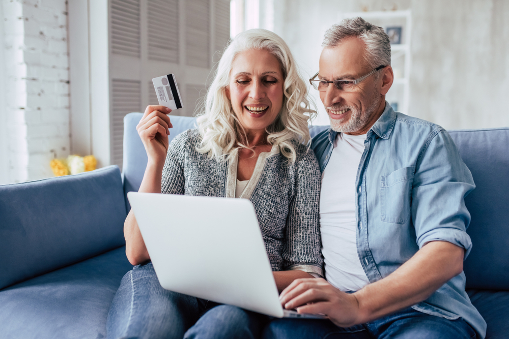 A senior couple where the woman is holding a credit card and the main is using a laptop computer
