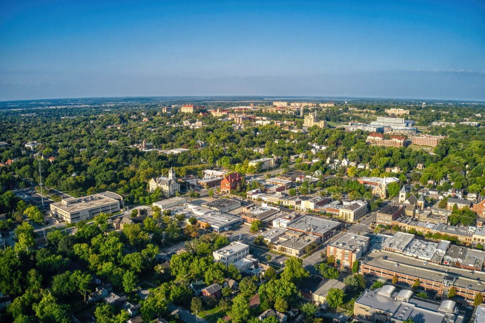 An aerial view of Lawrence Kansas showing many trees and college buildings
