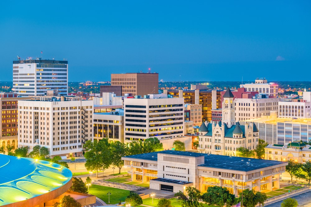 The skyline in Wichita Kansas, showing a blue sky, many buildings and a brightly colored circular building