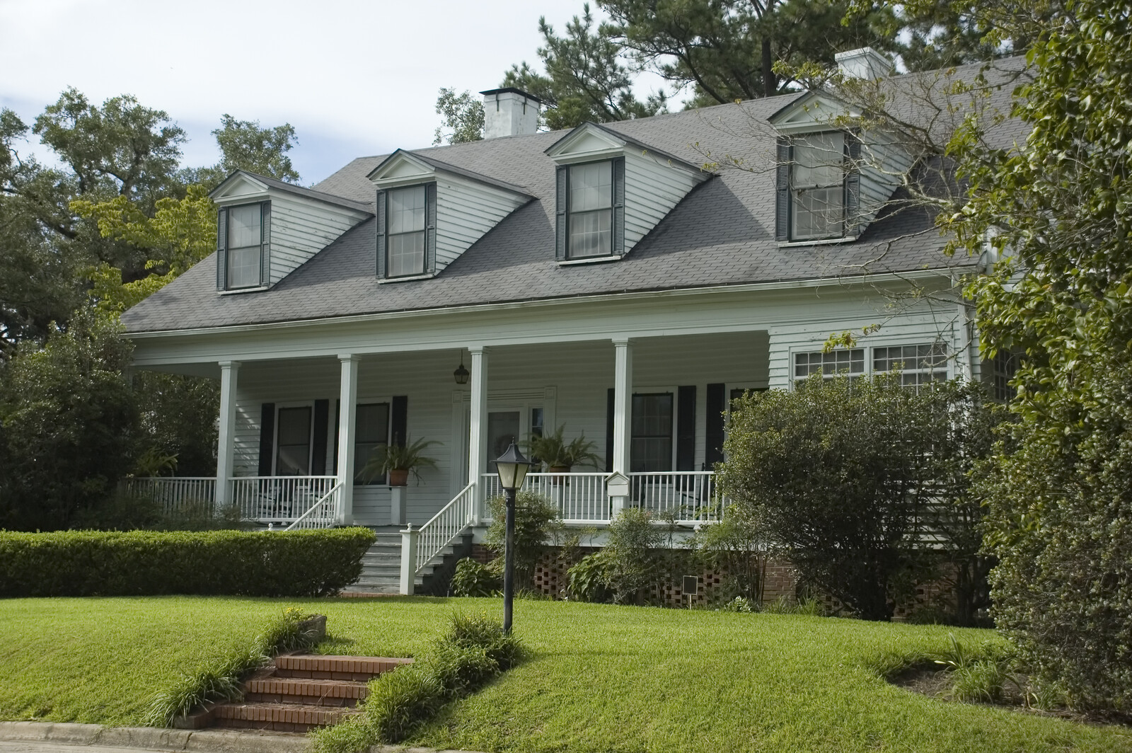 white home with gray shutters and green grass with trees and shrubs lining the yard