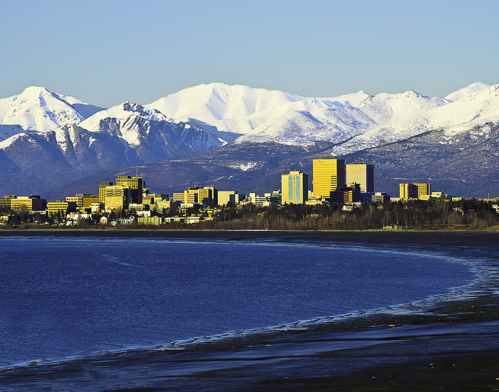 Anchorage skyline with mountains in the background and blue skies, photo taken from the other side of the bay