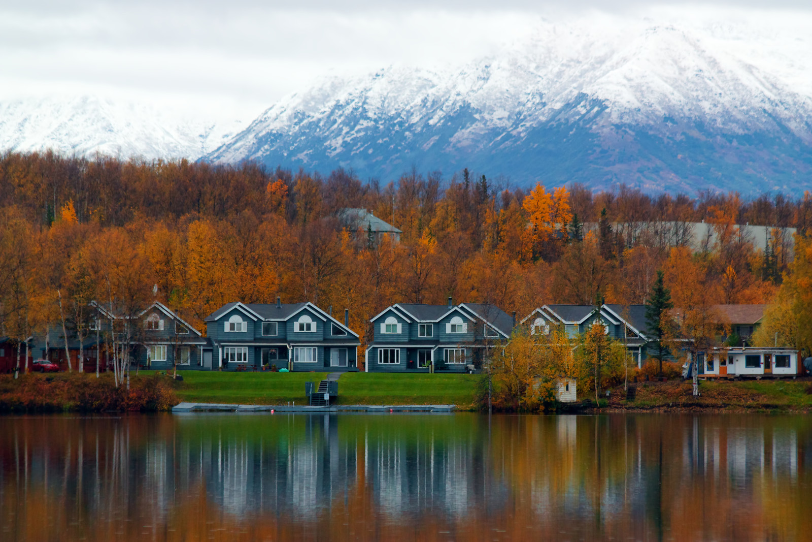 Top 5 Places to Retire in Alaska - Homes on the shore of  lake in wasilla with the mountains in the background surrounded by autumn colored trees