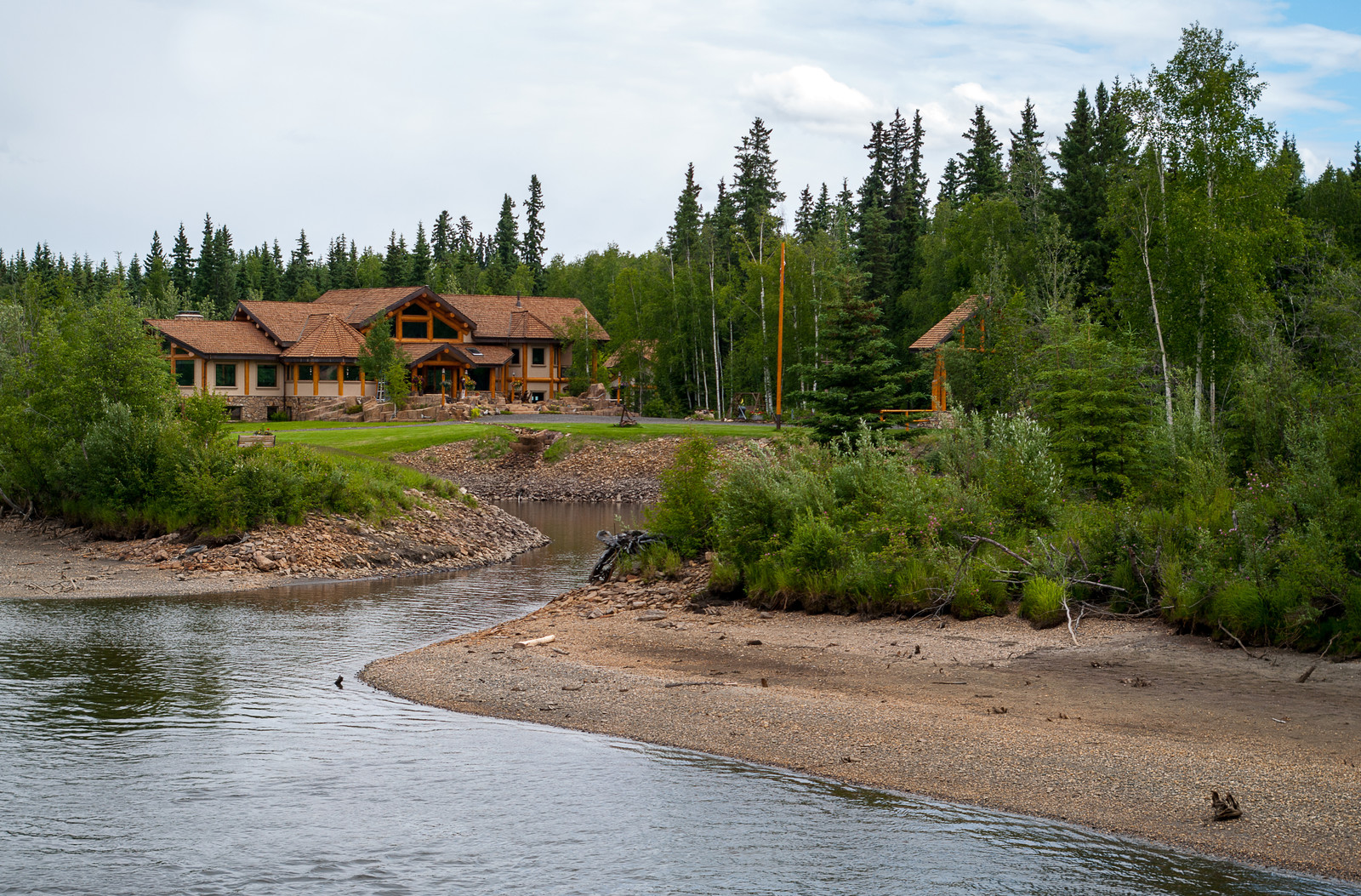 Log home along the river with a well-manicured front yard  and evergreens lining the banks and set in theback of the home and edge of the yard