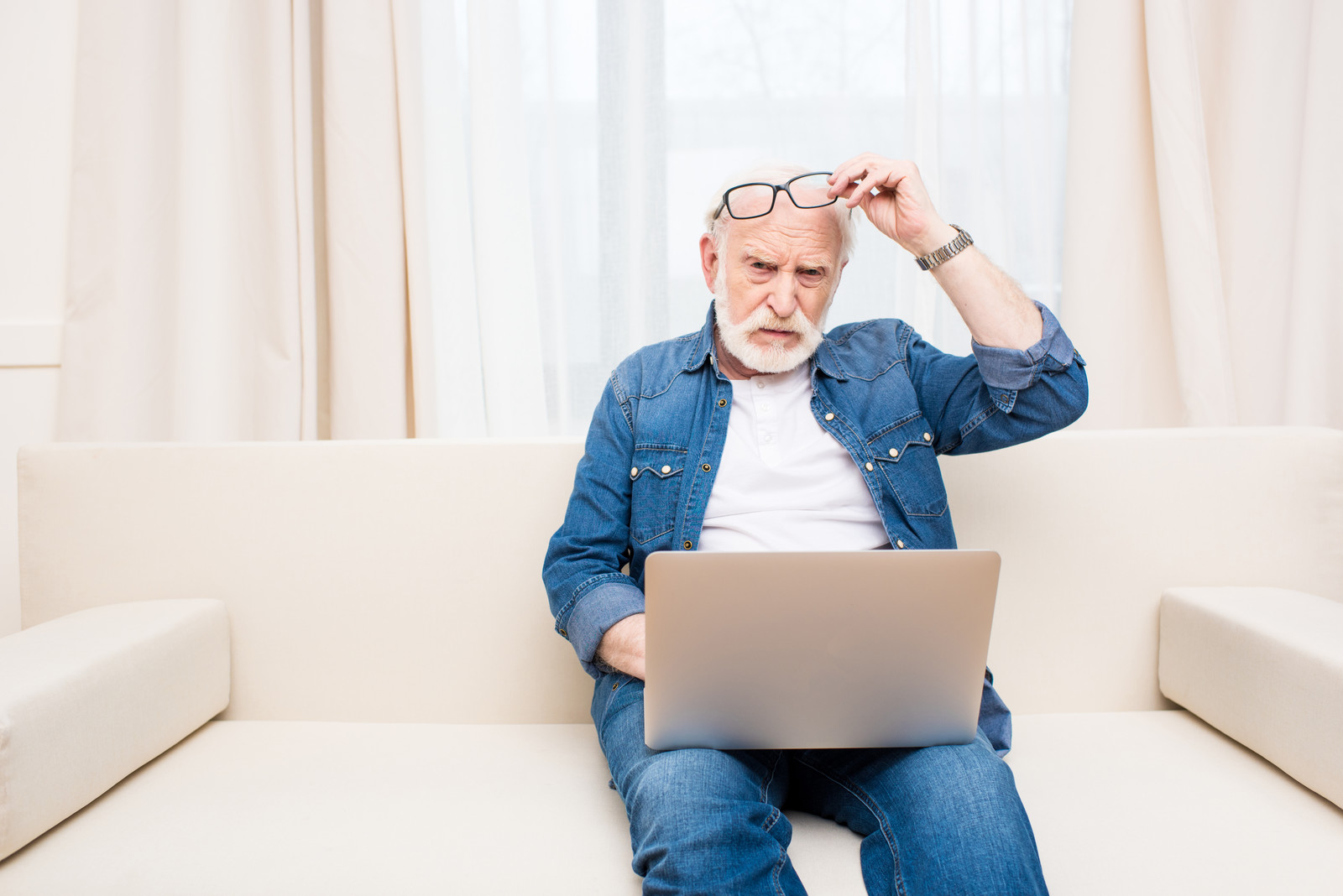Senior man taking reading glasses off the top of his head, while sitting on couch with laptop looking upset