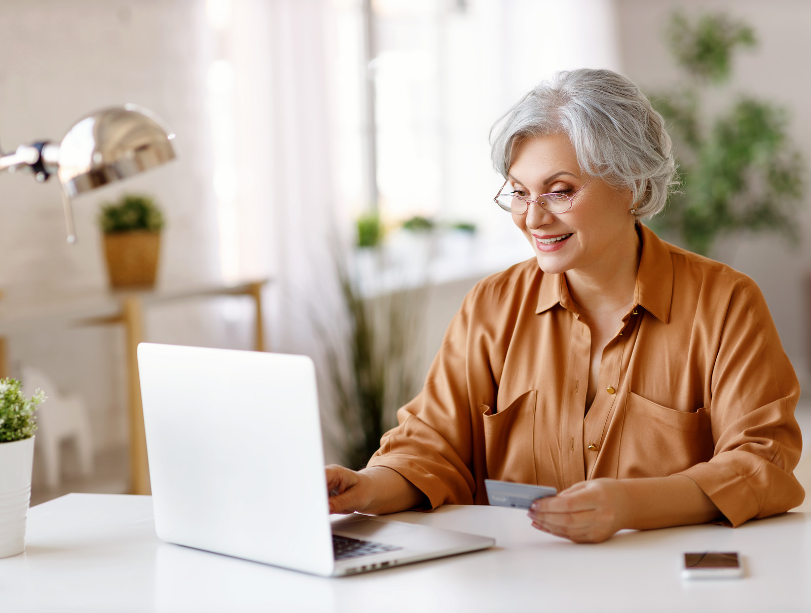 Smiling senior woman making a online payment on her laptop at home