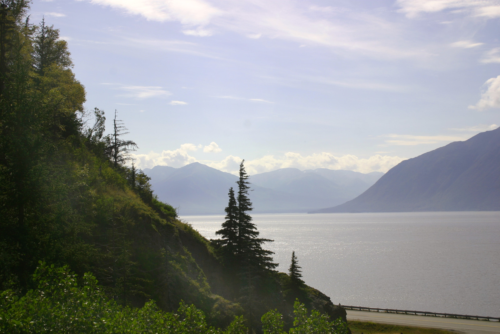 Sunny day looking over the bay in Kenai hill covered in green with trees and road at the base of the hill and mountains framing the other side of the bay