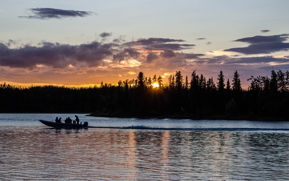 A boat going across the water in Kenai Alaska, where the sun is setting and everything is silhouetted