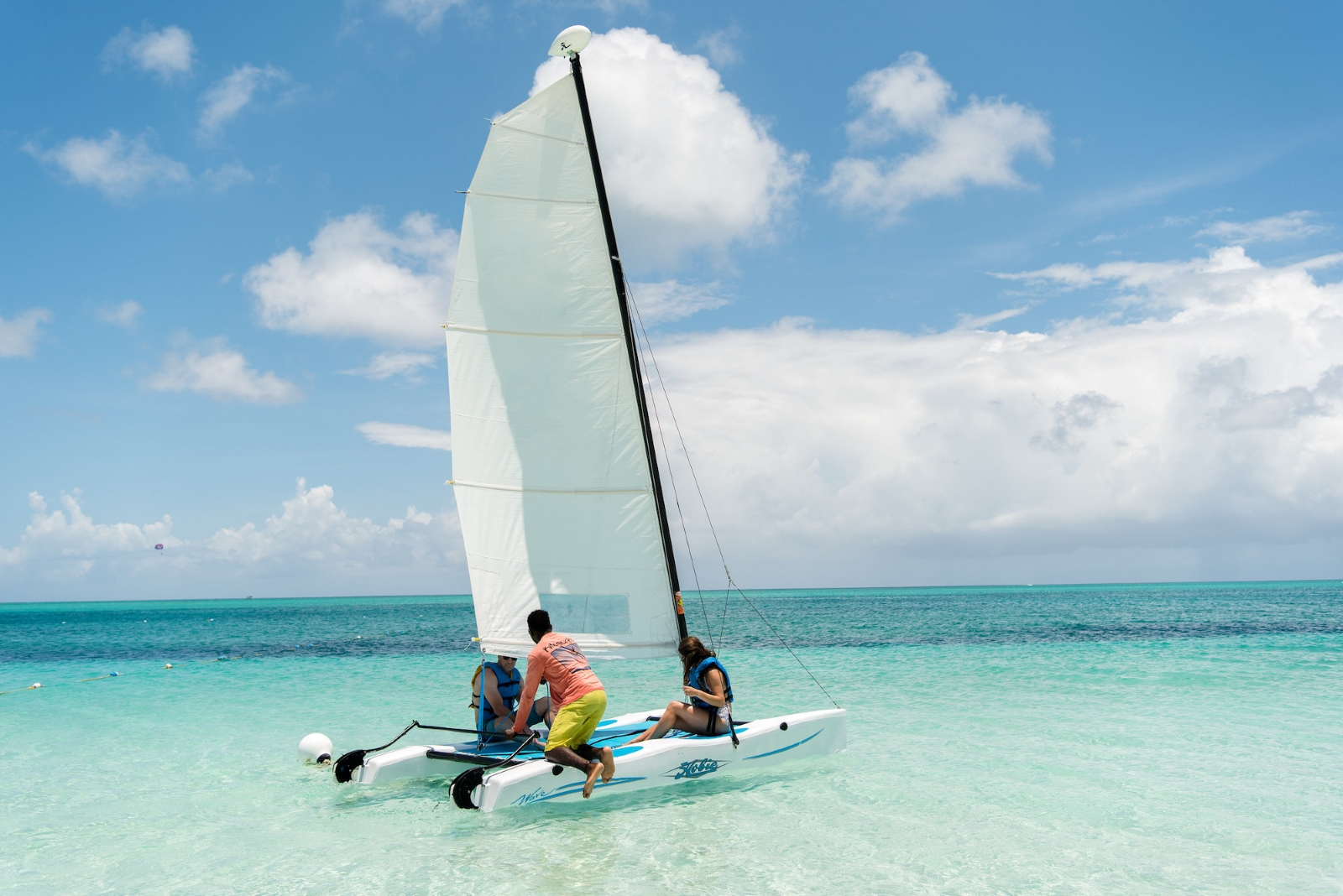 A couple getting ready to take a small sailboat out on clear blue waters with a person parasailing in the background