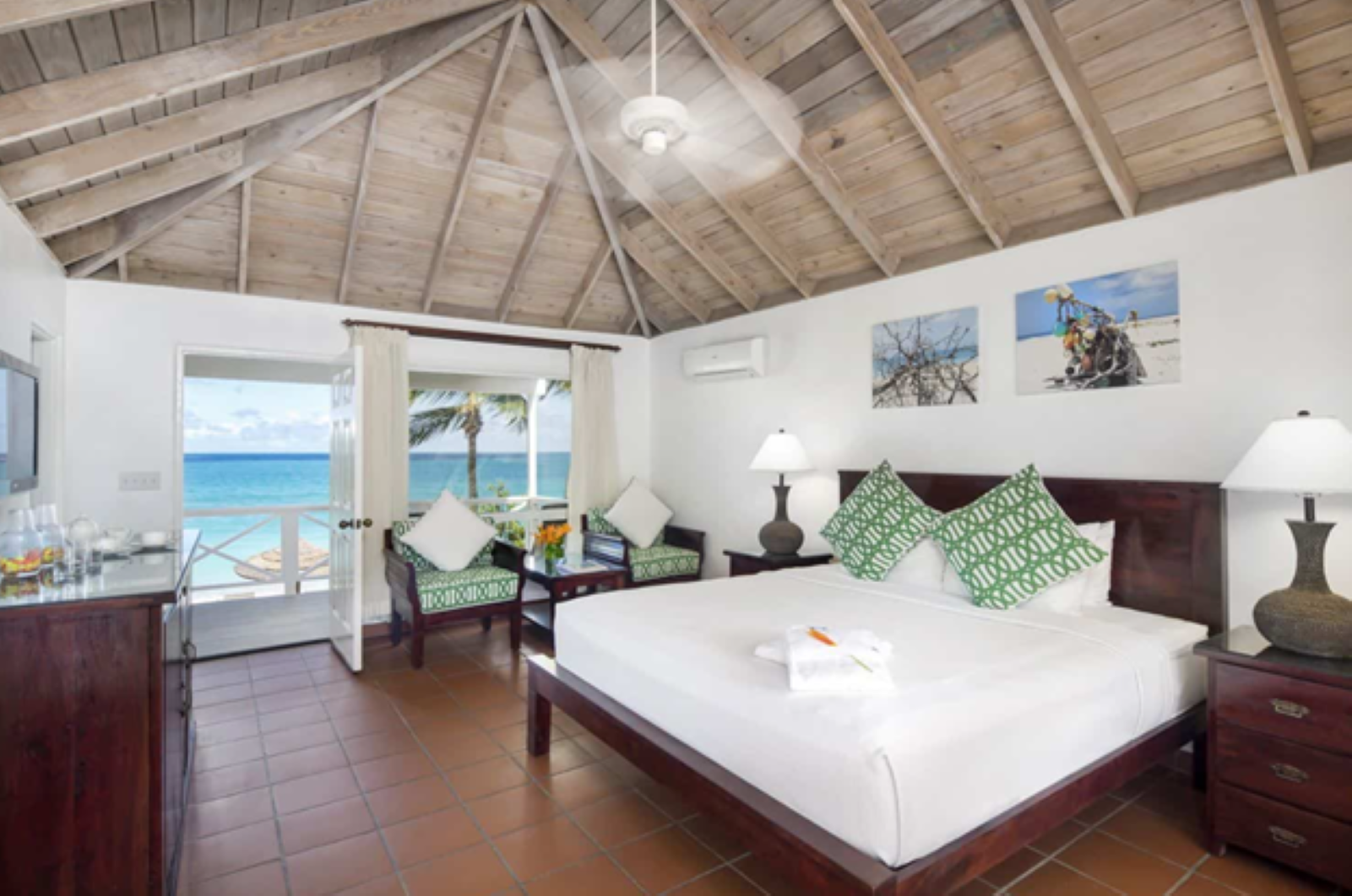 Cabana room with sitting chairs under the large window, king size bed, and brown tiled floor with an open door leading to the terrace
