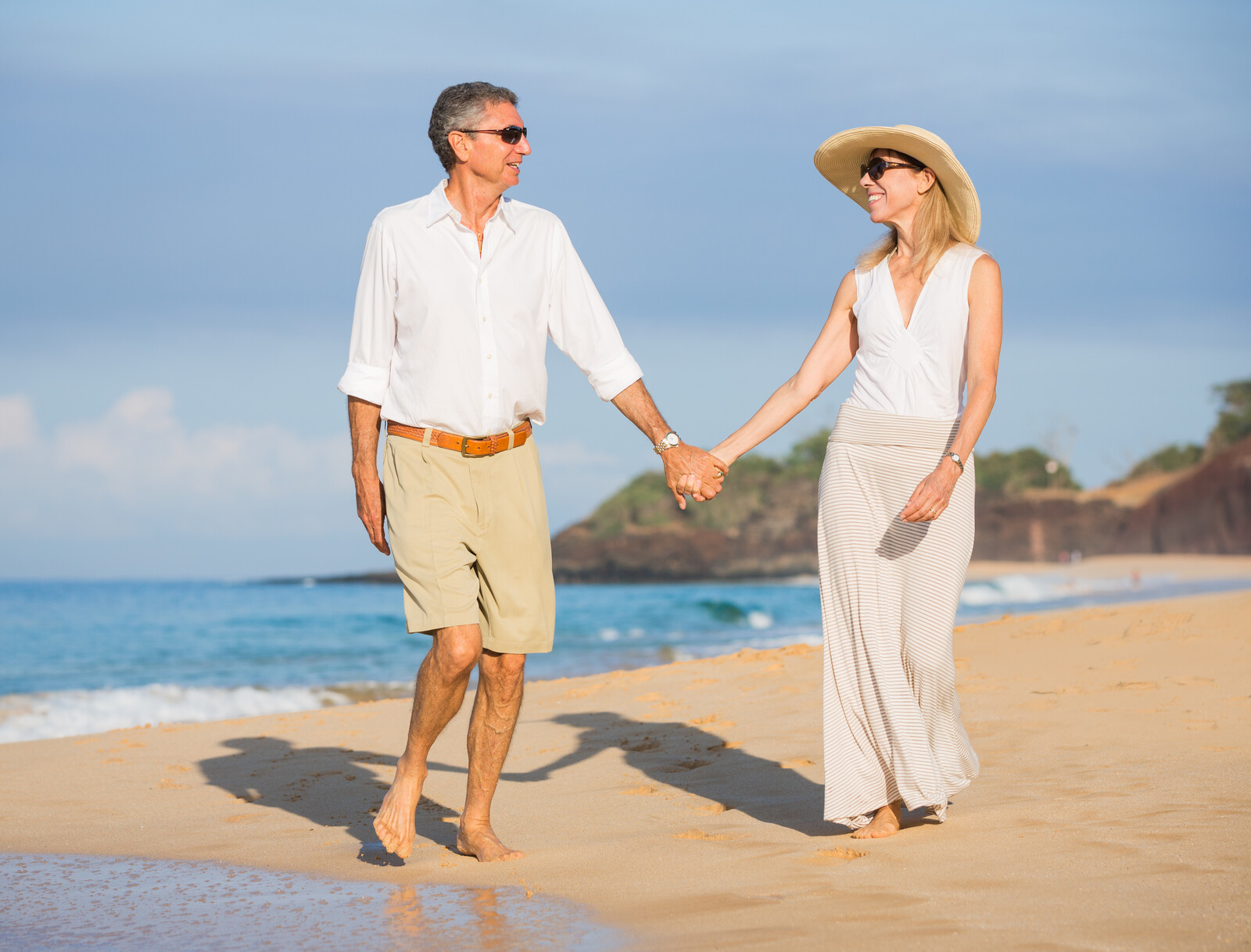 Best All Inclusive Adults-Only Resorts - Happy senior couple holding hands on a Caribbean beach with the ocean in the background.  The woman is wearing sunglasses and a hat the man is wearing sunglasses, the two are looking at one another
