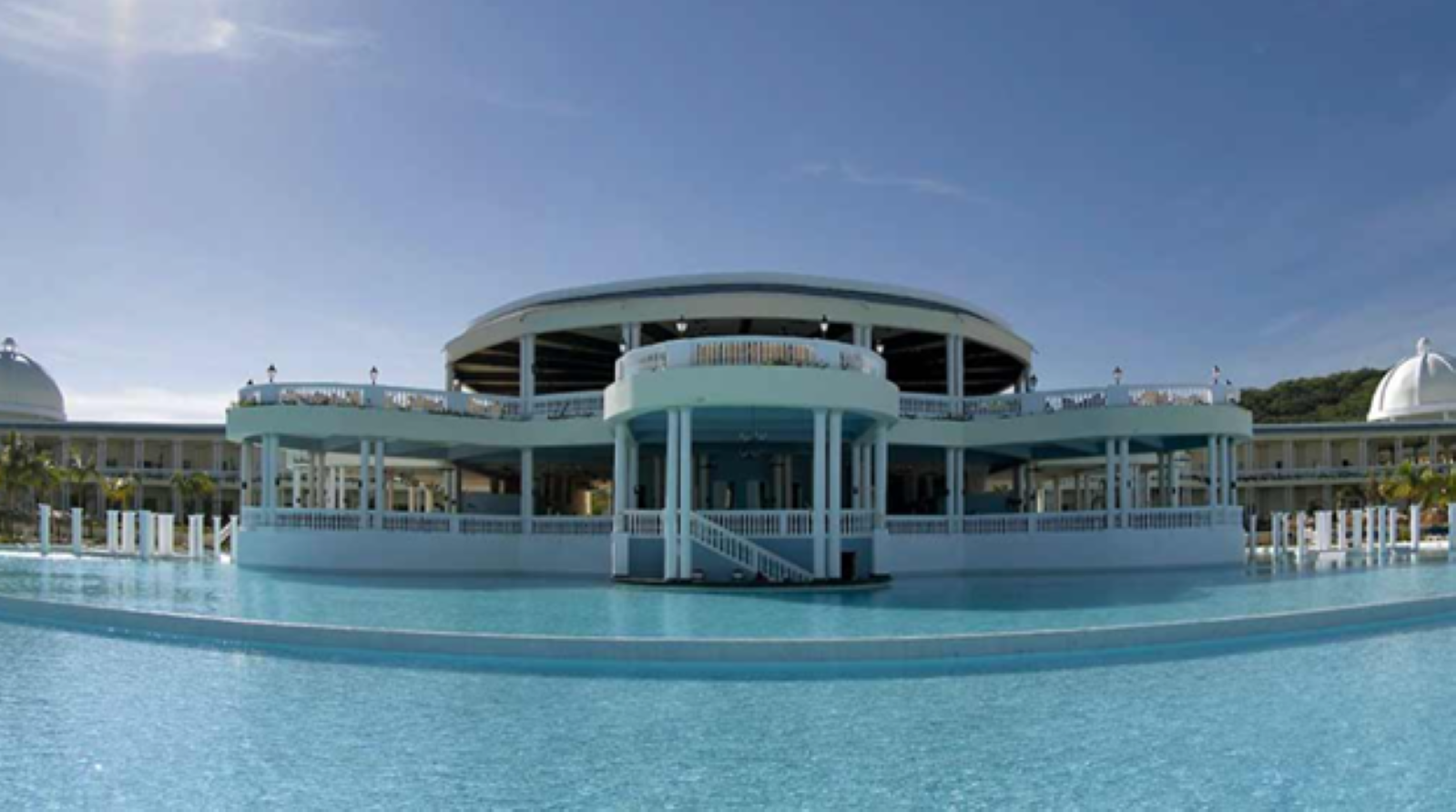 Large wading pool in front of a large rounded two story balcony with outdoor seating