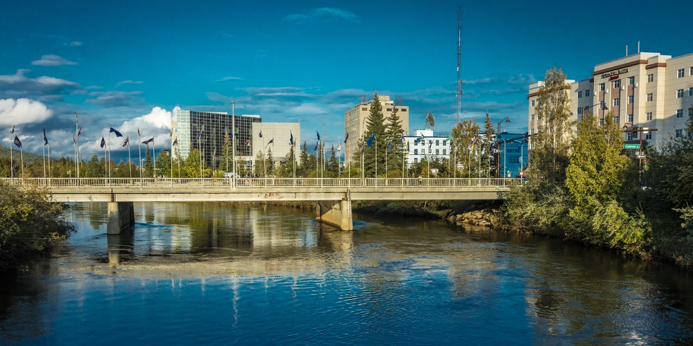 Looking across the water in Fairbanks Alaska, showing building and a bridge with various flags