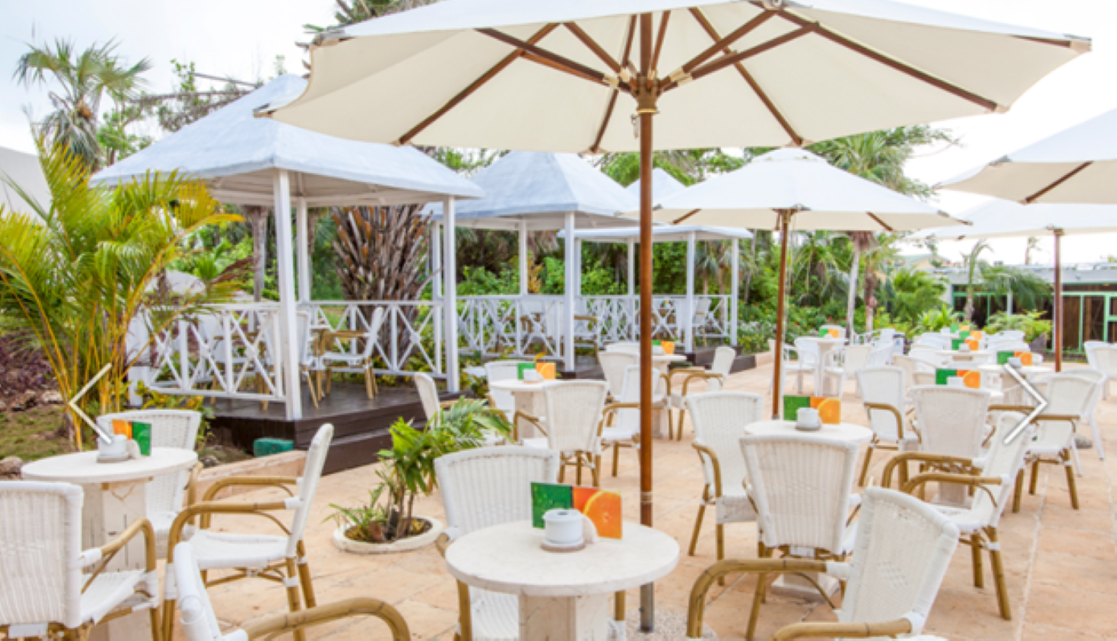 Outdoor dining with raised private dining areas set off to the left, the tables, chairs, and umbrellas are all white with wood accents