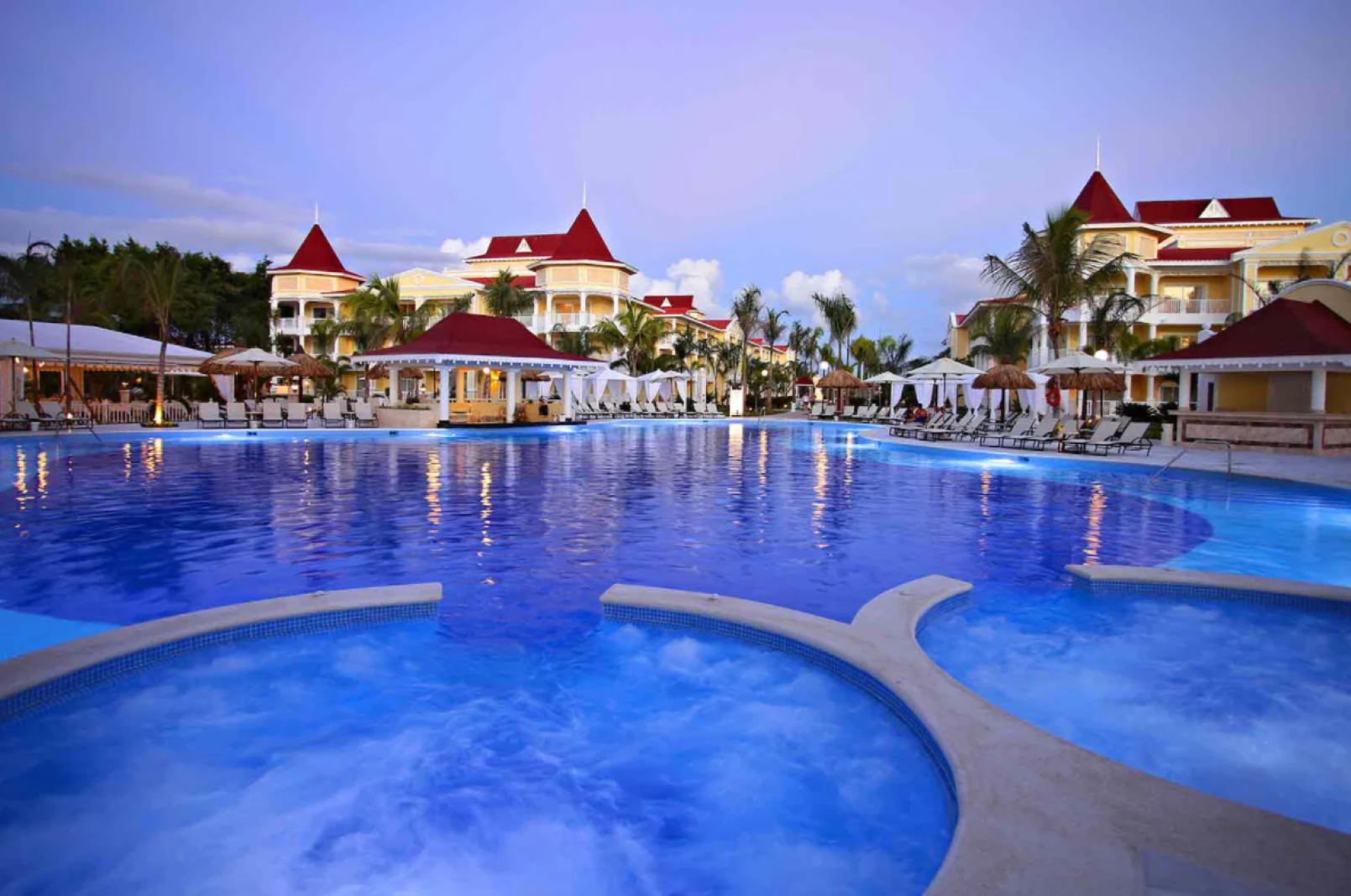 Photo taken at dusk showing hot tubs connected to the a main pool. The large pool is lined with chairs, umbrellas, and has a swim up bar. The grounds have palm trees lining the walkways and the sky is a light lavender with soft white clouds. the hotel sits on both sides of the pool and is yellow with white trim and a red roof.