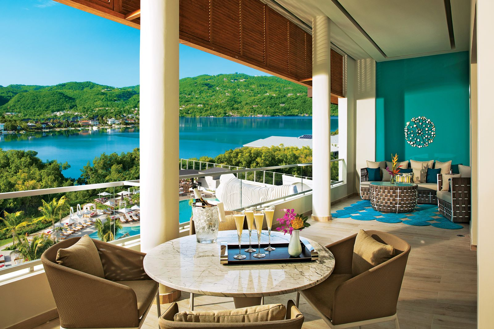 Colorfully private furnished Balcony with small dinette table with champagne flutes and bottle, plus sitting area on the right side of the terrace, overlooking the hotel pool area and bay.