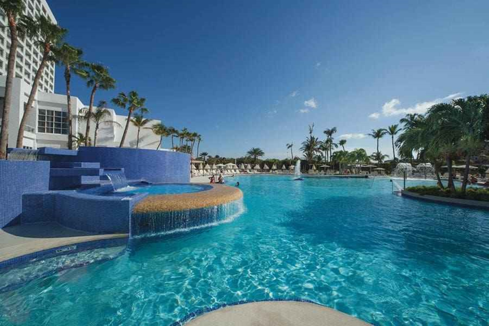 Riu Pool with fountains, on the right lounge chairs with palm trees and on the left the hotel with balconies.