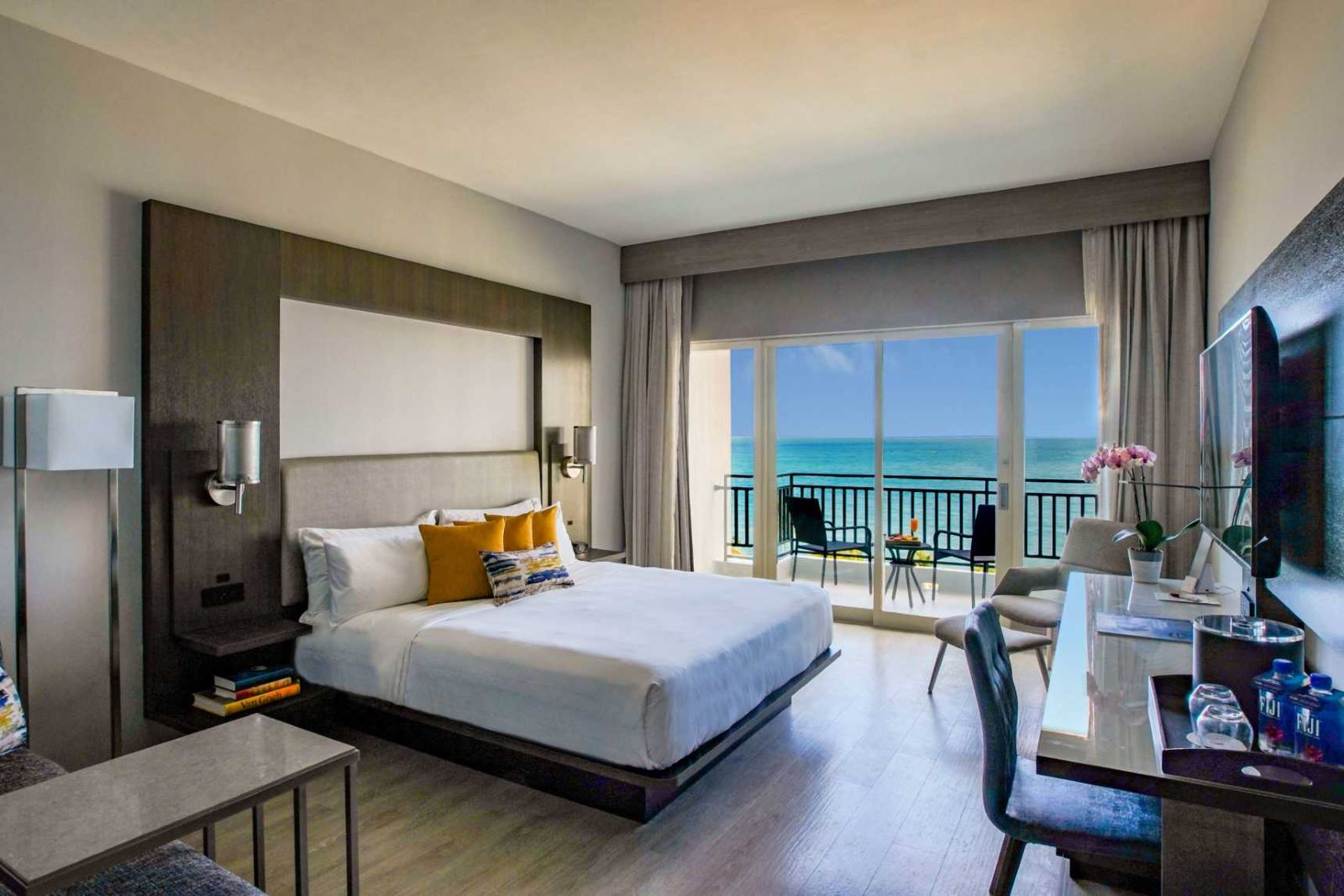 San Juan Marriott resort hotel room with a king size bed and sliding glass door showing the balcony with sitting area overlooking the clear blue water and blue sky
