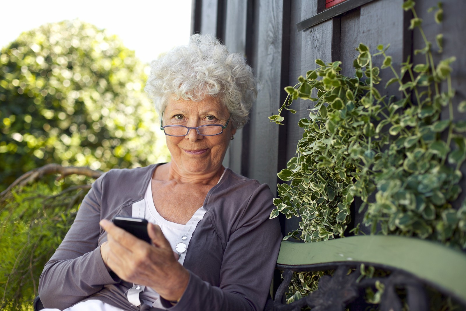 New Texting Scams Seniors Need to Know About Now - Senior woman enjoying the outdoors sitting on a bench in the shade texting on her smart phone