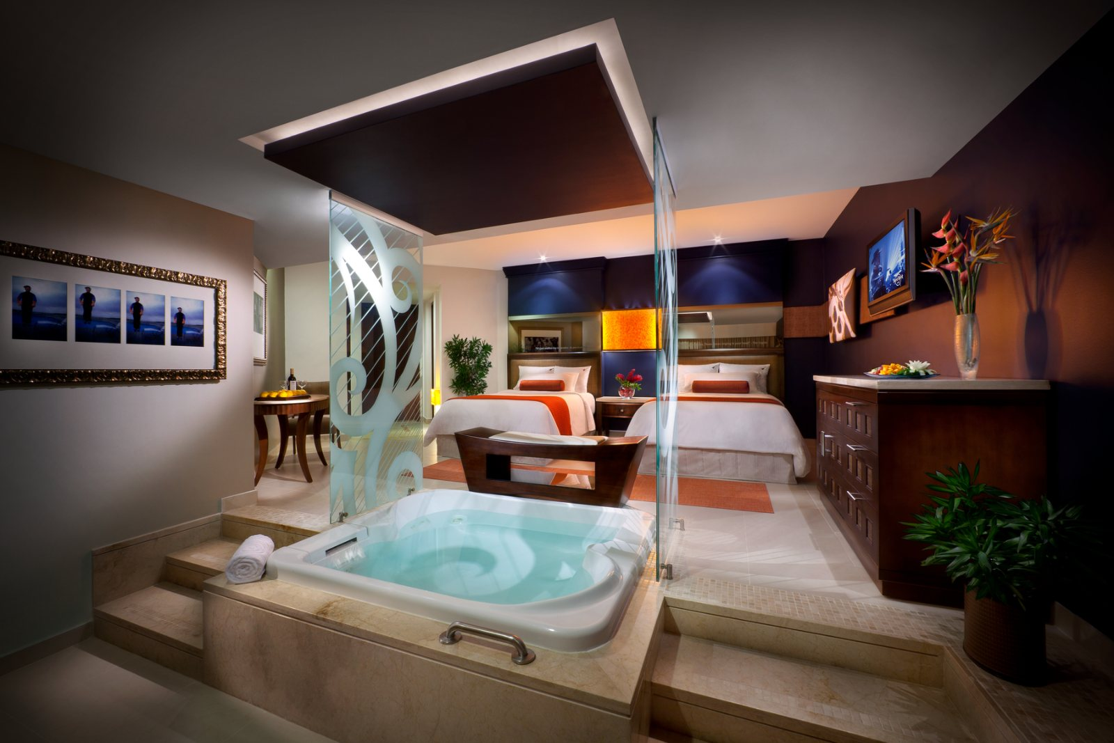 A luxury Suite in the hard rock hotel featuring two beds a large burau and a step in hot tub framed on two sides with decorative glass guards