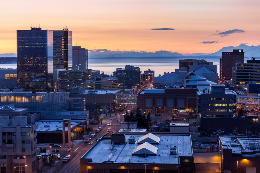 The skyline in Anchorage Alaska during dawn or dusk, where there are plenty of buildings and vehicles on the street