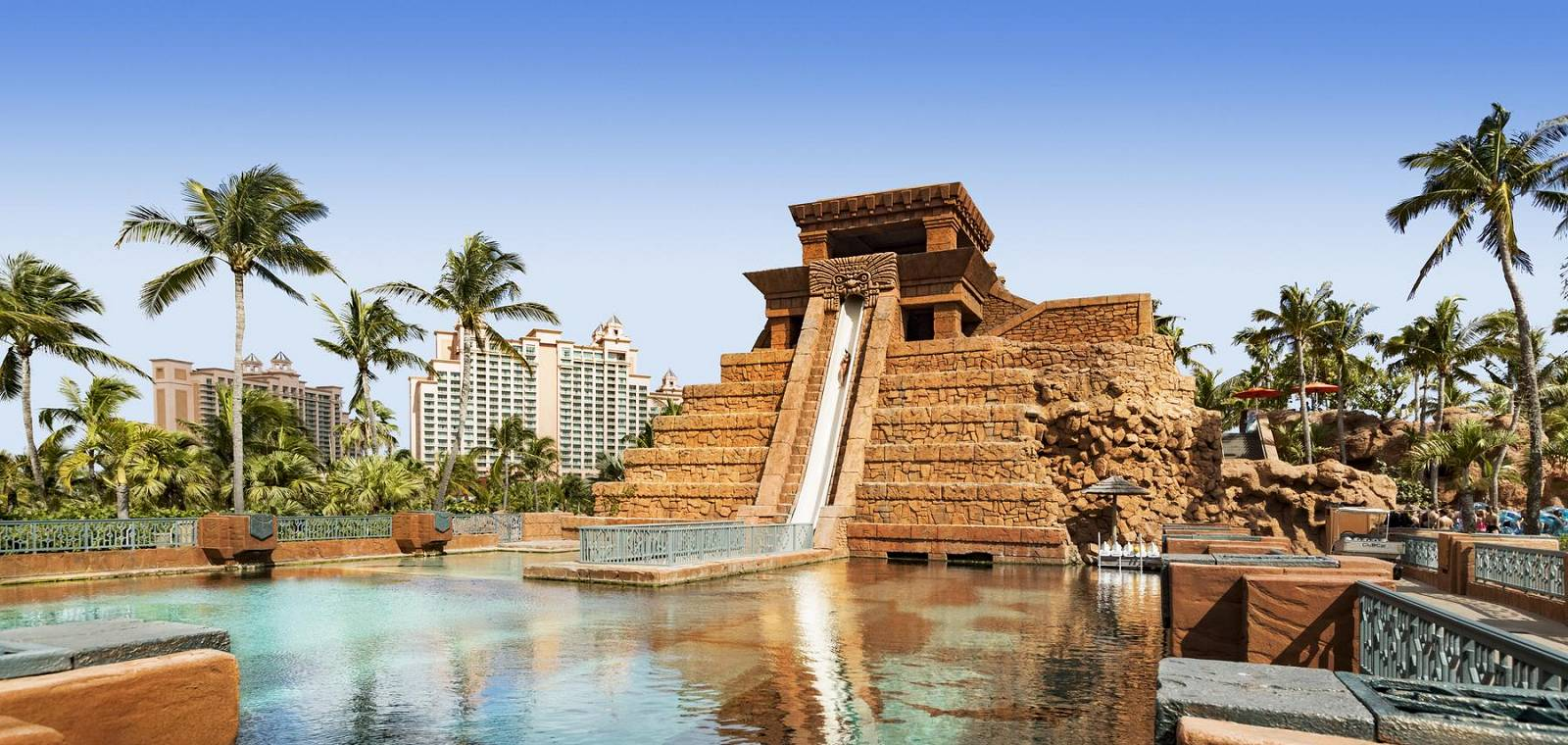 Water park pyramid slide at the Atlantis paradise island hotel with the hotel featured in the background and palm trees framing the water slide