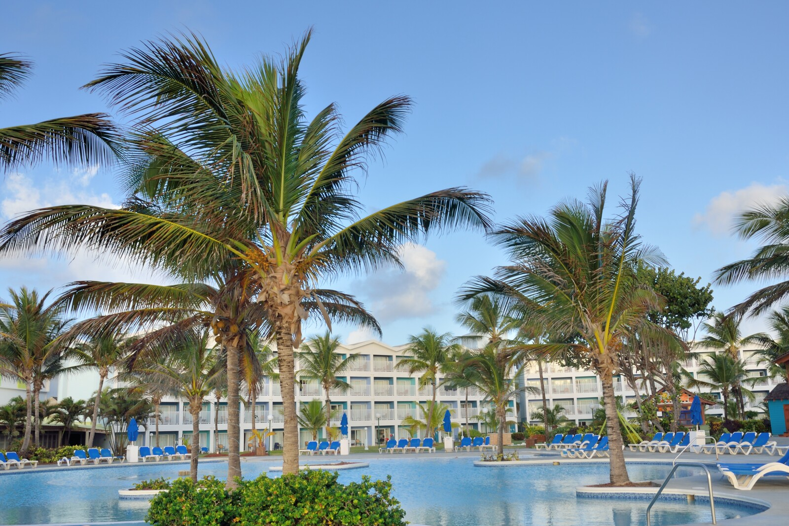 White Caribbean hotel with balconies sitting in the background of the large pool surrounded by blue  deck loungers